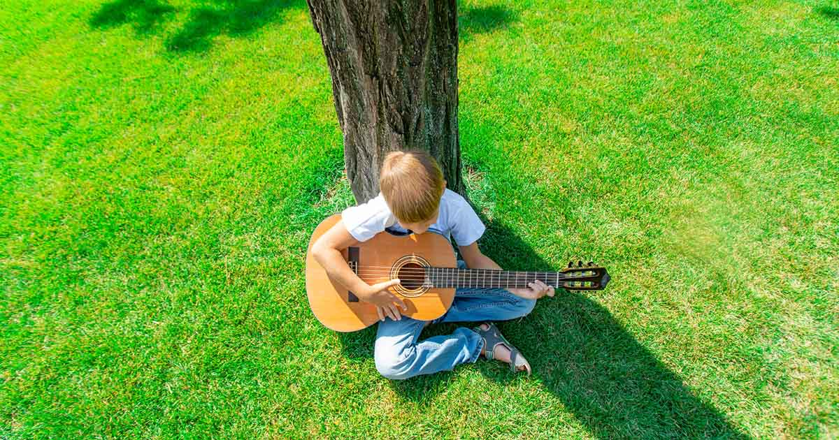 boy playing a guitar sits under a tree